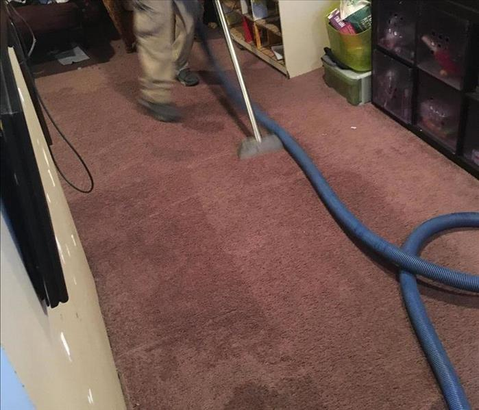 SERVPRO technicians with extraction equipment on a wet carpet