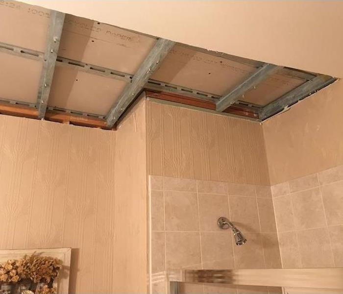 Bathroom with ceiling studs exposed over shower