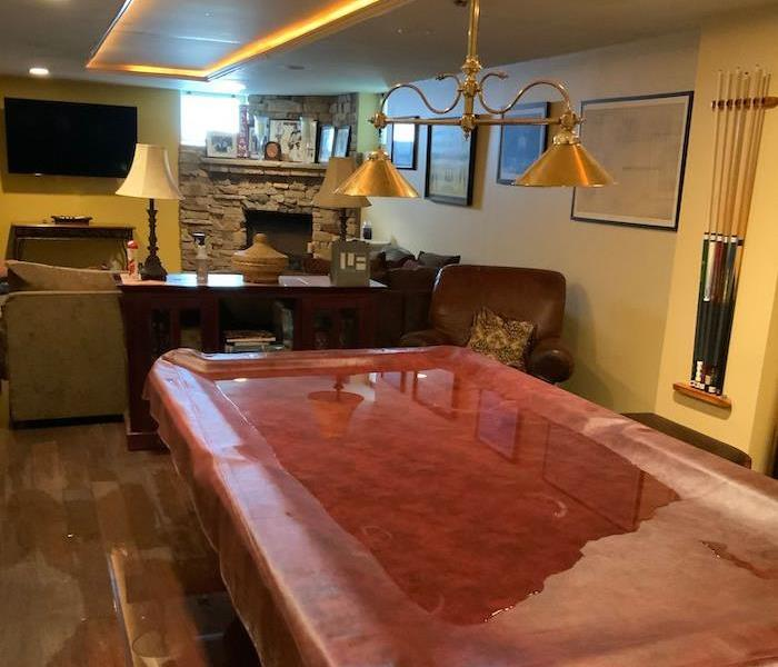 Pool table cover on hardwood floor with standing water
