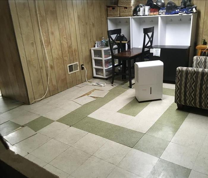 Floor with loose tiles and SERVPRO equipment