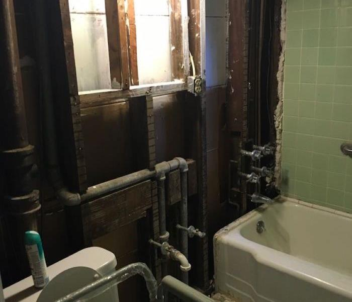 Bathroom with much of the structure removed and framework exposed