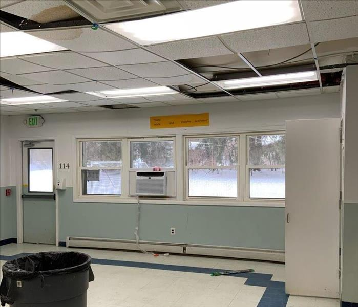 Classroom with window air conditioner unit and ceiling tiles with water spots