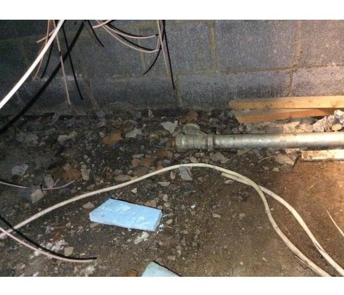 Crawlspace floor with pipe, debris, and dirt