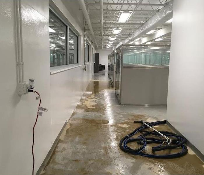 Office walkway with cubicles and water on concrete floor with hose