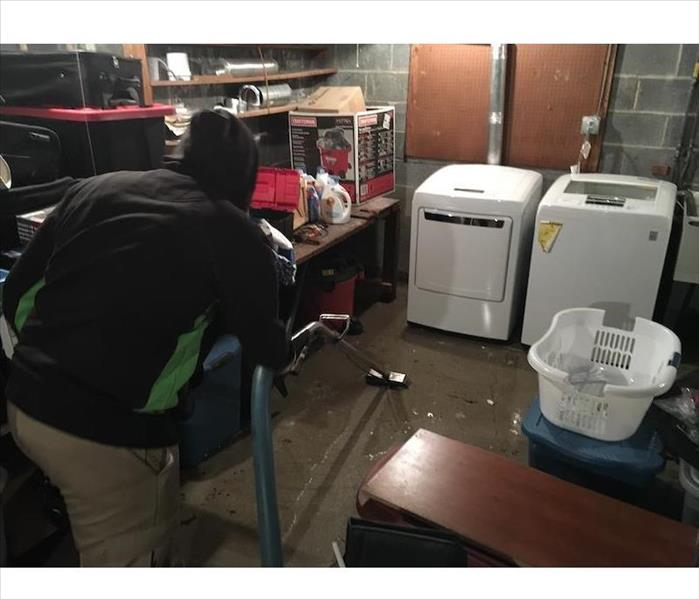 SERVPRO employee extraction water from basement laundry room