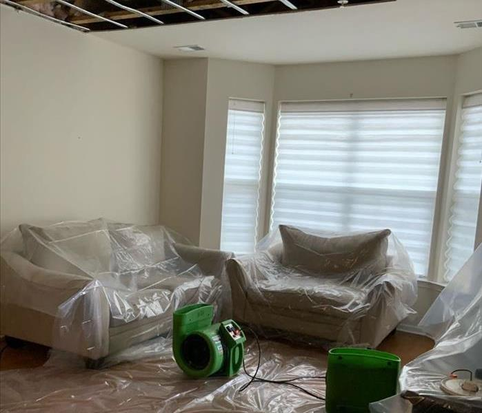 Living room with SERVPRO drying equipment by sofa and chair covered in plastic on the hardwood floor