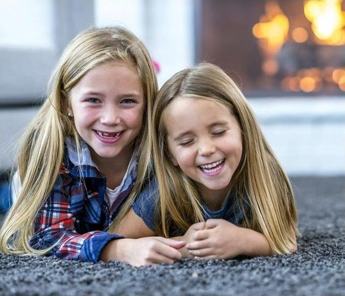 two young girls lying on carpeted floor